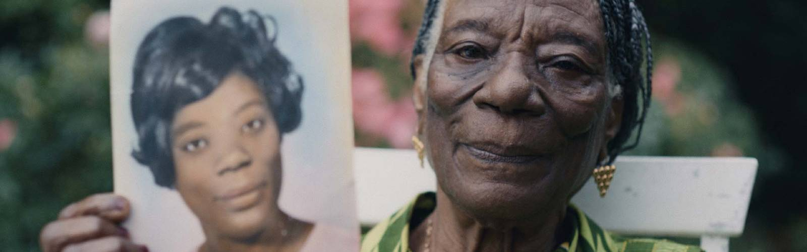 Linneth, an older Black woman, holds up a photo of herself from when she was young