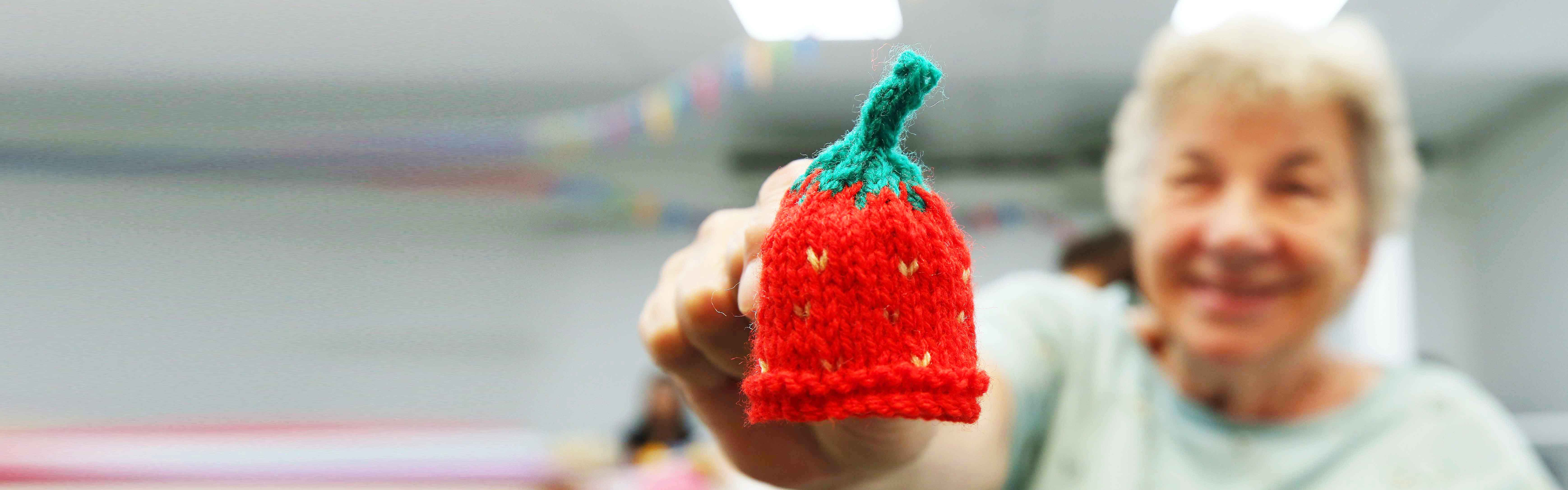 an older lady holds up a small knitted hat to the camera
