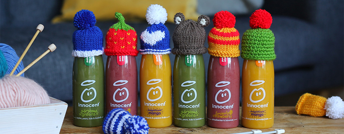 Photo of 6 innocent smoothie bottles with little knitted hats on top of each