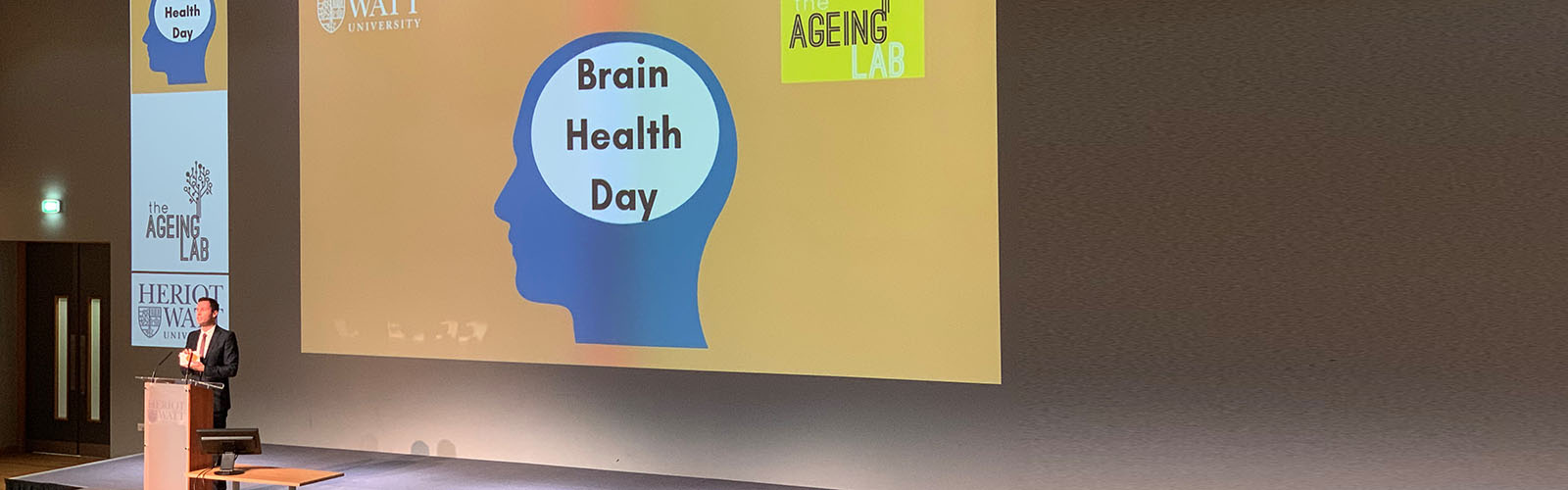 Professor Alan Gow from Heriot-Watt University stands in front of a screen with the headline 'Brain Health Day' showing