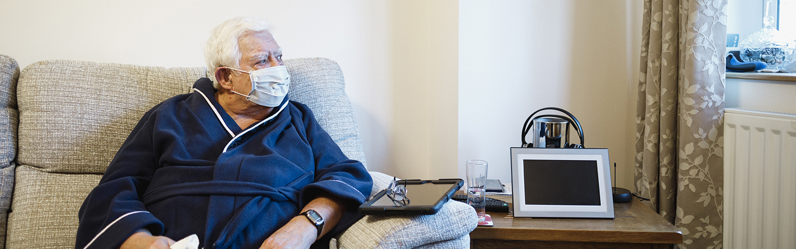 An older man, sat on a sofa and wearing a protective face mask