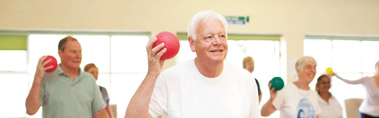 A man doing exercises with a red ball at an exercise class