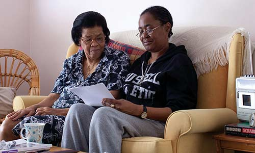 Two women sat on a sofa together, reading a letter