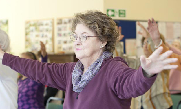 Woman doing arm exercises at an Age UK exercise class