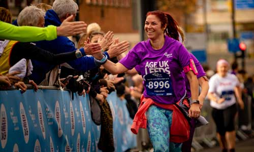 Woman giving high fives to the crowd whilst running in the Age UK Leeds Abbey Dash