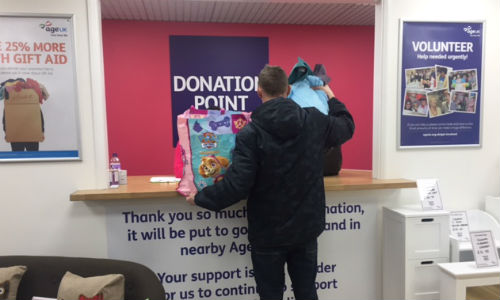 A man donates items to his Age UK shop
