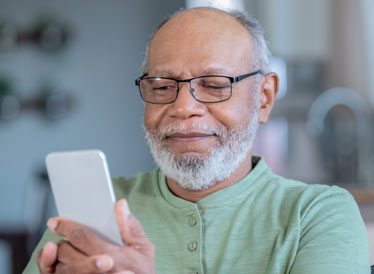 Man smiling using smartphone to download an app