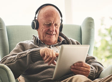 Man on tablet using headphone