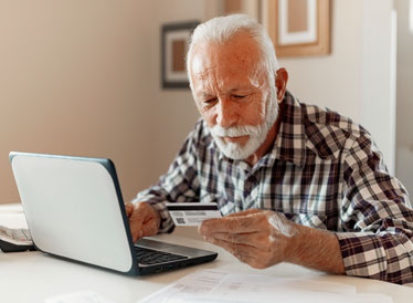 Man at laptop looking at bank card