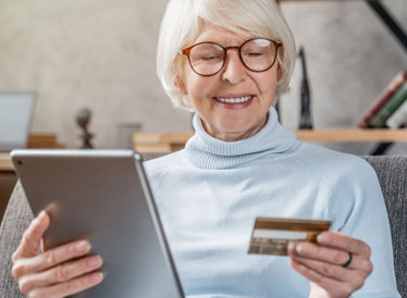 Woman holding tablet and credit card whilst online shopping