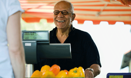 man smiling while selling peppers at a grocery stall