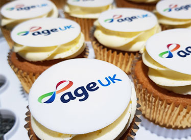 CUpcakes in gold foil with Age UK logo on top